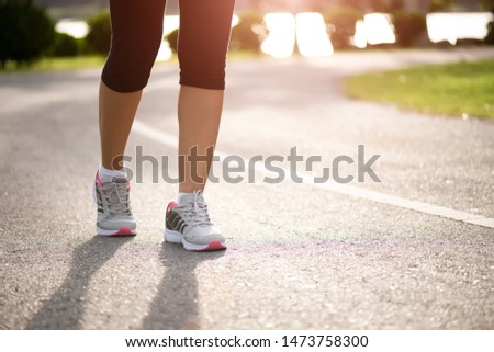 Closeup woman walking towards on the road side. Step, walk and outdoor exercise activities concept. #1473758300