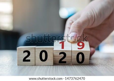 Business man hand holding wooden cube with flip over block 2019 to 2020 word on table background. Resolution, strategy, solution, goal, business, New Year New You and happy holiday concepts #1473762470