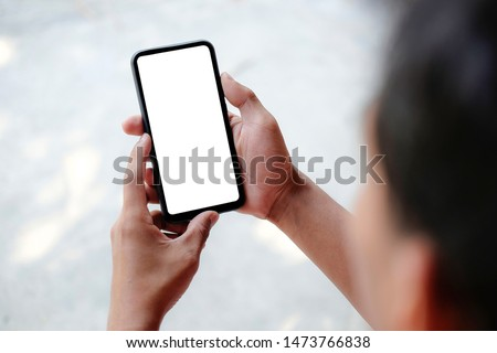 Mock up smartphone of hand holding black mobile phone with blank white screen #1473766838
