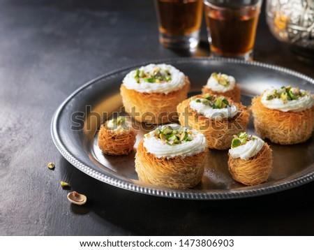 Kataifi, kadayif, kunafa, baklava pastry nests cookies with pistachios with tea. Cooking sweets turkish, or arabic traditional ramadan pastry dessert on a dark background. #1473806903