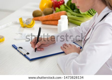cropped view of dietitian in white coat writing in clipboard at workplace #1473828134
