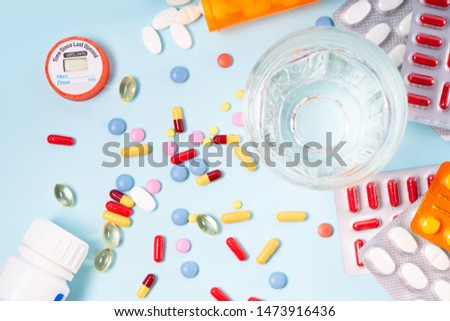 Colorful pills with glass of clear water over blue background. Medical pharmacy concept, top view flat lay #1473916436