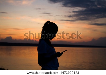 Silhouette of a young woman on sunset background with a mobile phone in her hands. Royalty-Free Stock Photo #1473920123