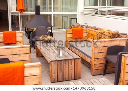 Outdoor restaurant terrace with wooden furniture in scandinavian style. Eco-friendly authentic design. #1473963158