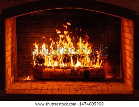Glowing fire in a huge stone fireplace #1474005908