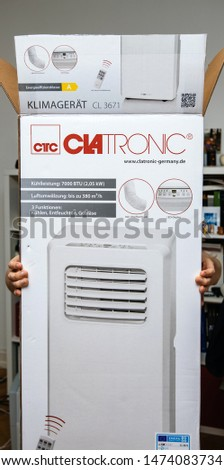 Paris, France - Jun 23, 2019: Young man holding unboxing installing new portable air conditioner unit AC during hot summer in his living room Clatronic #1474083734