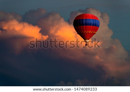 Fantastical image of an ornate red and blue hot air balloon floating high in beautiful storm clouds glowing in purple, pink, yellow, and orange colors at sunset #1474089233