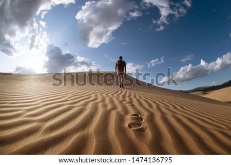 One lonely man walks in desert on dunes #1474136795
