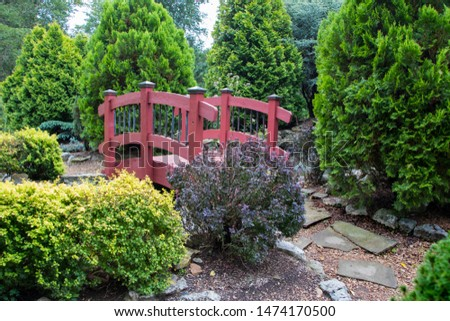 Rocky path leading up to small red bridge in garden surrounded by trees. #1474170500