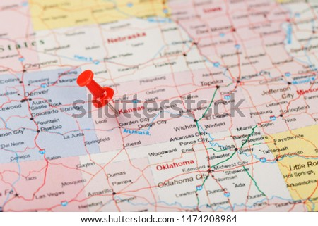 Red clerical needle on a map of USA, Kansas and the capital Topeka. Close up map of Kansas with red tack, United States map pin USA #1474208984