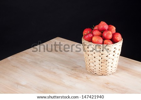 Strawberries in basket on wooden table #147421940