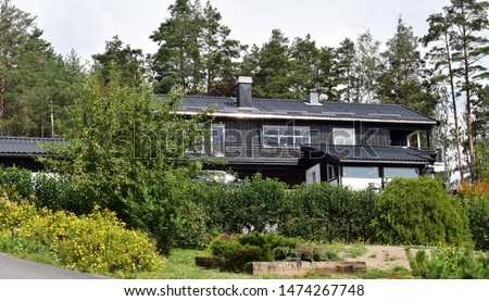 Black residential house home exterior, front, entrance and facade with green garden in sunny and summer season - Norway Norwegian #1474267748