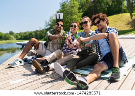 leisure, picnic and technology concept - friends with drinks taking picture by selfie stick on lake pier in summer park