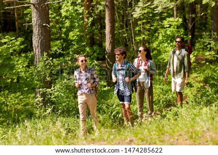 travel, tourism, hike and people concept - group of friends walking with backpacks in forest #1474285622