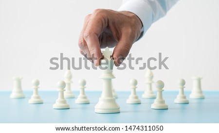 Closeup of male hand holding white chess figure of king positioned in front of the other figures on a blue desk in a conceptual image. Royalty-Free Stock Photo #1474311050