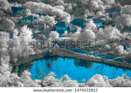Infrared photography of the houses at the lake .