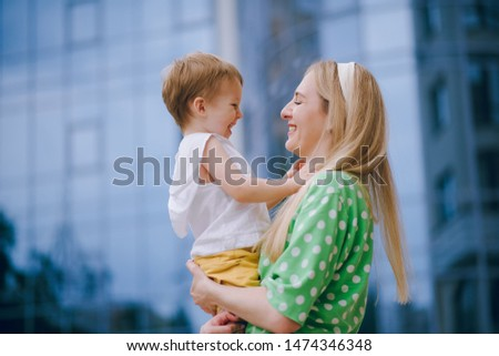 Pretty mom and son running around, jumping, cuddling near the mall.  Pretty mom hugged her little son and kissed gently. #1474346348