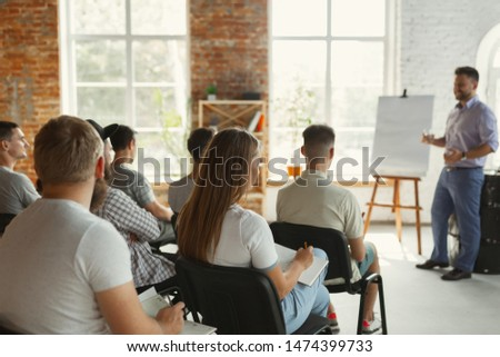 Male speaker giving presentation in hall at university workshop. Audience or conference hall. Rear view of unrecognized participants in audience. Scientific conference event, training. Education #1474399733