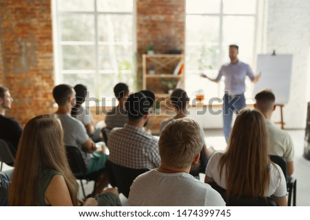 Male speaker giving presentation in hall at university workshop. Audience or conference hall. Rear view of unrecognized participants in audience. Scientific conference event, training. Education #1474399745