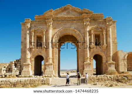 Jerash, Jordan - August 19, 2012: Tourists visit arch of Hadrian in the ancient Roman city of Gerasa in Jerash, Jordan. #1474468235