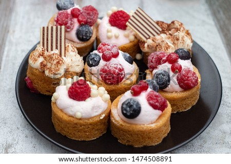 Cclose up of tiny cupcakes with various berries #1474508891