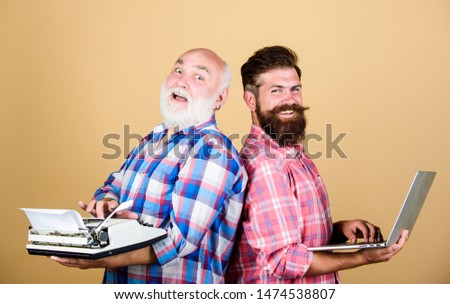 Business partners. technology battle. Modern life. youth vs old age. business approach. father and son. two bearded men. Vintage typewriter. retro typewriter vs laptop. New technology generation. #1474538807
