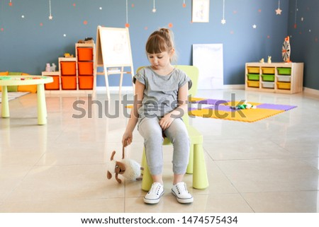 Sad little girl with autistic disorder in playroom #1474575434