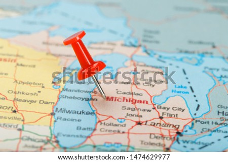 Red clerical needle on a map of USA, Michigan and the capital Lansing. Close up map of Michigan with red tack #1474629977