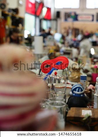 Flea market, interior. Blurred environment, in the center of the picture stands a carnival mask.
