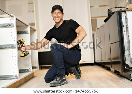 A Male Carpenter Drilling In Cabinet With Electric Cordless Drill #1474655756