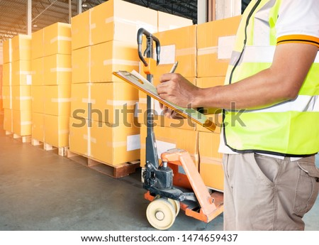 Warehouse Cargo Courier Shipping and  Transportation, Stack cardboard boxes on pallet, worker man hand holding clipboard with inventory management products at distribution warehouse. #1474659437
