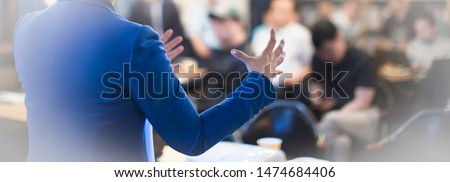 Speaker giving a talk at a corporate business conference. Audience in hall with presenter in front of presentation screen. Corporate executive giving speech during business and entrepreneur seminar. #1474684406