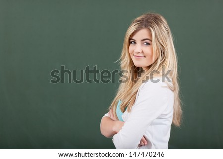 Smiling young beautiful blond girl student with folded arms standing confidently in front of a blank green blackboard