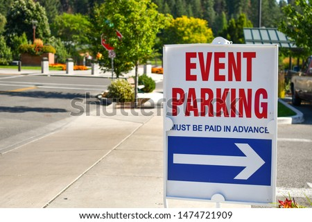 A red, white and blue parking sign on a street sidewalk points towards event parking on a sunny day in a non-descript mountain town.