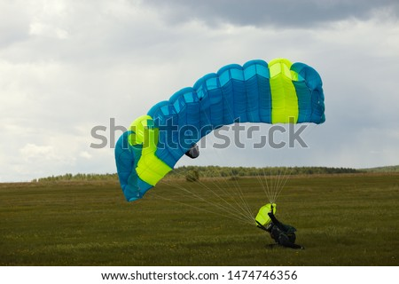 Skydiver tries to extinguish the parachute canopy after landing in windy weather. #1474746356