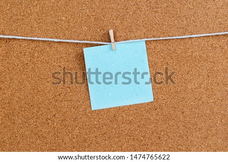 Corkboard with blue color stickers fixed by a pin. Square shaped sheets stuck on a billboard by colored thumbtacks. Notice board with empty reminder note. #1474765622