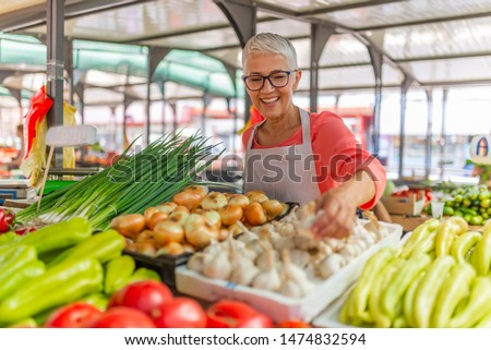 Friendly woman tending an organic vegetable stall at a farmer's market and selling fresh vegetables from the garden. Female Stall Holder At Farmers Fresh Food Market #1474832594