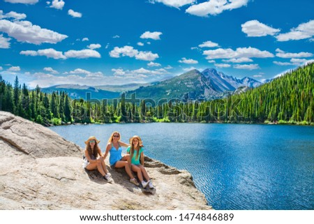 People sitting and relaxing by the lake. Smiling family enjoying time together on hiking trip. Beautiful summer mountain landscape. Bear Lake, Rocky Mountains National Park, Colorado ,USA. #1474846889