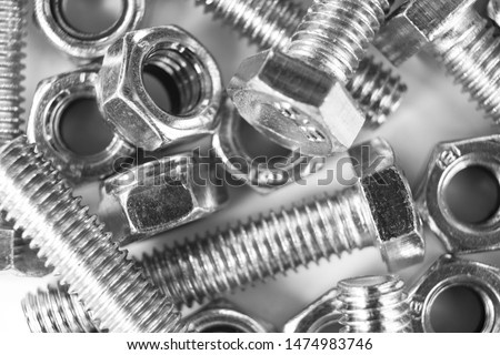 Metal bolts and nuts  in a row background. Chromed screw bolts and nuts isolated. Steel bolts and nuts pattern. Set of Nuts and bolts. Tools for work. Black and white #1474983746