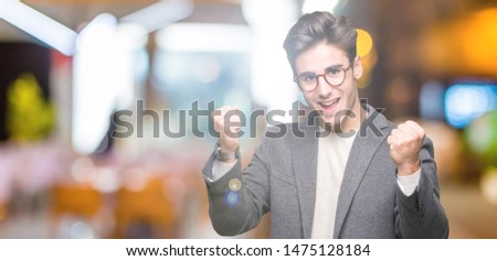 Young business man wearing glasses over isolated background celebrating surprised and amazed for success with arms raised and open eyes. Winner concept. #1475128184