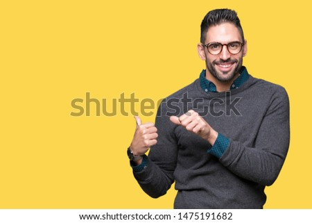 Young handsome man wearing glasses over isolated background Pointing to the back behind with hand and thumbs up, smiling confident #1475191682