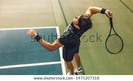 Top view of young tennis player jumping to hit the ball from the baseline of a hard court. Professional tennis player about to hit the ball for the serve. #1475207318