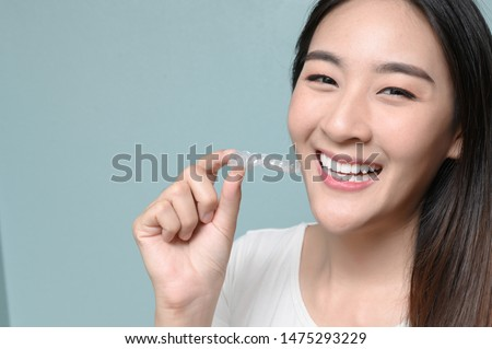 Woman wearing orthodontic silicone trainer. Mobile orthodontic appliance for dental correction. tooth whitening systems. #1475293229