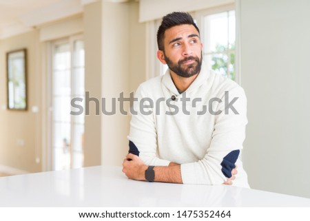 Handsome hispanic man wearing casual white sweater at home smiling looking side and staring away thinking. #1475352464