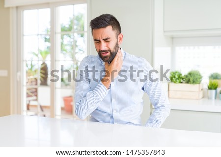 Handsome hispanic business man Touching painful neck, sore throat for flu, clod and infection Royalty-Free Stock Photo #1475357843
