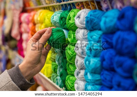 Close Up of yarn balls. Girl hand choosing Yarn in Knitting Shop. knitting shop center. A lot of color yarn for knitting. Selection of colorful yarn wool on shopfront #1475405294