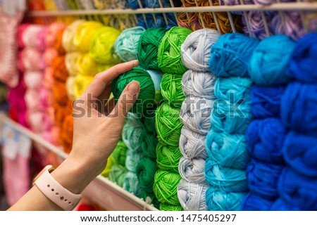 Close Up of yarn balls. Girl hand choosing Yarn in Knitting Shop. knitting shop center. A lot of color yarn for knitting. Selection of colorful yarn wool on shopfront #1475405297