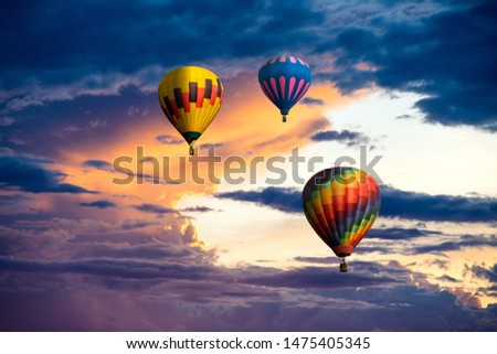 A group of three colorful hot air balloons ascending into a sunset sky with beautiful dramatic clouds #1475405345