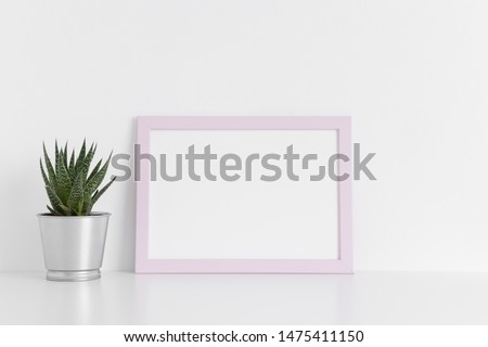 Pink frame mockup with a cactus in a pot on a white table.Landscape orientation. #1475411150