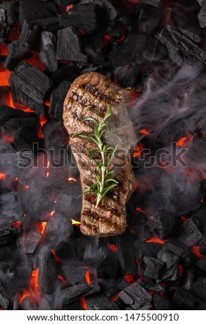 Fried meat steak on a black background of charcoal. Cooked juicy steak with smoke on the coals with rosemary. Grilled delicious marinated steak on coals, closeup photo. Top view #1475500910